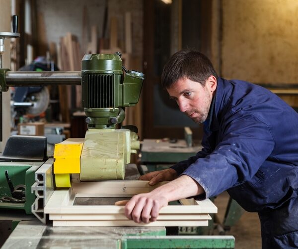 Portrait of Carpenter man cutting wooden window with tablesaw in workshop